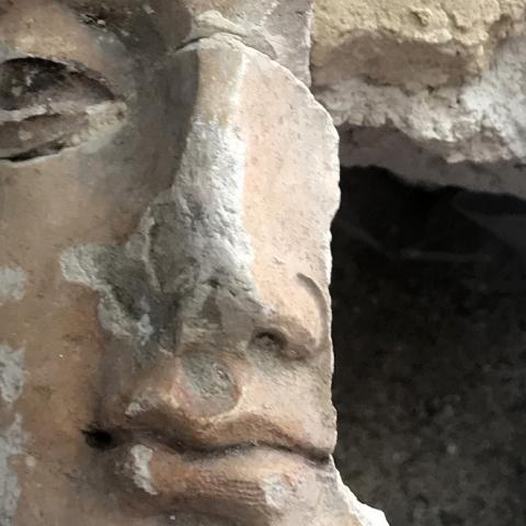 close-up on the face of a cracked plaster statue of a Buddha, with part of its cheek missing