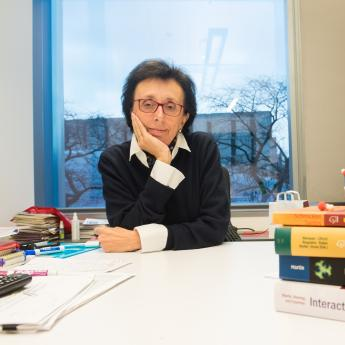 Prof. Giulia Galli sits in her office with a pile of textbooks and a model of molecules.