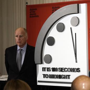 Three people stand at the newly unveiled Doomsday Clock