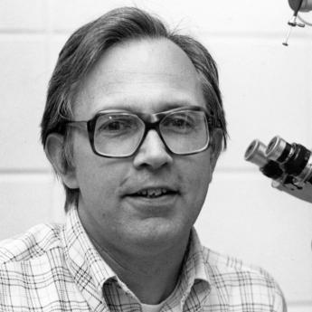 B&W photo of Prof Anderson in glasses and button-down next to a microscope