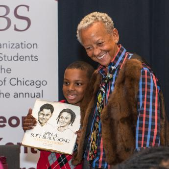 Poet Nikki Giovanni with a child following the 2020 George E. Kent Lecture